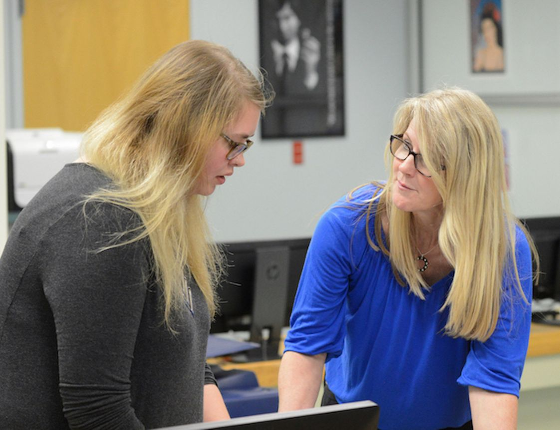 Western Nevada College Photo #1 - Western Nevada College Graphic Communications professor Jayna Conkey (left) helps a student.